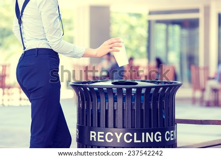 Closeup cropped image woman's hand throwing empty paper coffee cup in recycling bin, isolated outside, trees background. Recycling, eco friendly approach concept. Keep streets, city, earth clean - stock photo