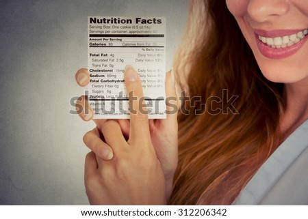 Closeup cropped portrait image woman reading healthy food nutrition facts isolated on gray wall background  - stock photo