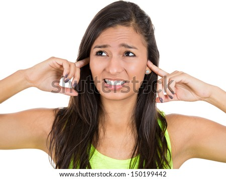 Closeup cropped portrait of young unhappy, stressed woman covering her ears looking away, as if to say, stop making that loud noise it's giving me a headache, isolated on a white background - stock photo