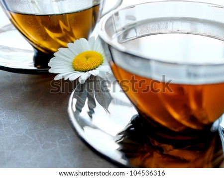 Closeup cups of tea with a camomile between two saucers - stock photo