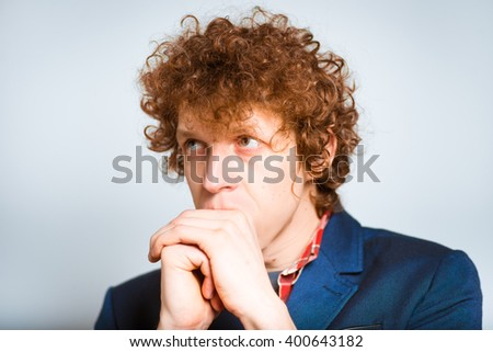 closeup curly man worried, isolated on background - stock photo