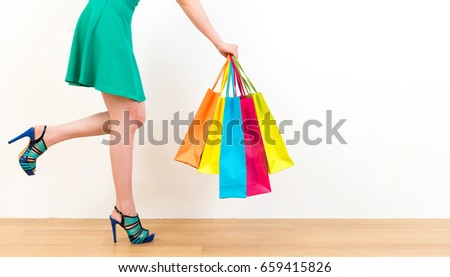 closeup cut photo of happy consumer woman showing many multi colored shopping bags standing on wooden floor with white wall background.
