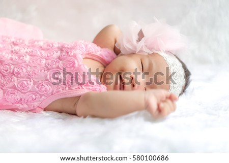 Closeup cute asian baby girl wearing Flower headband on white wool carpets,baby fashion concept