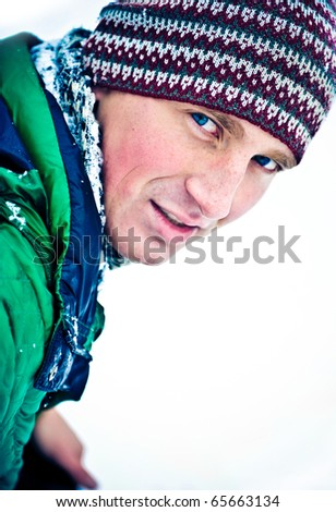Closeup cute portrait of beautiful fashionable sportsman outdoor in winter park white snow behind on background