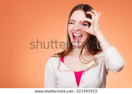 Closeup cute woman looking through imaginary binocular funny looking through fingers simulating glasses orange background - stock photo