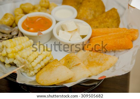 Closeup delicious food platter of typical latin foods such as corn, empanadas, abbas, cheese and salsas nicely arranged. - stock photo