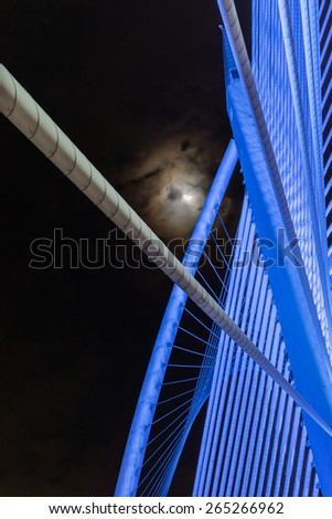 Closeup design of Sri Wawasan bridge at Putrajaya, Malaysia.  A night view showing blue color light on the steel structure with the moon and dark sky at the background. - stock photo