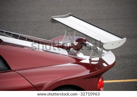 Closeup detail of a custom racing spoiler on the rear of a sports car.  Shallow depth of field. - stock photo