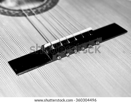 Closeup detail of a guitar. Music theme and background in black and white colors.. - stock photo