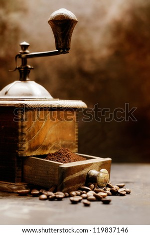 Closeup detail of a vintage coffee grinder with beans spilling from the open drawer. Neutral browns tone antique effect. - stock photo