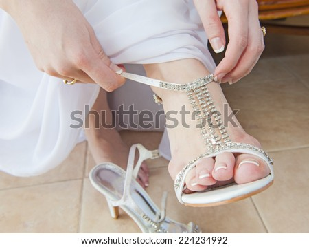 Closeup detail of bride putting on high heeled sandal wedding shoes - stock photo