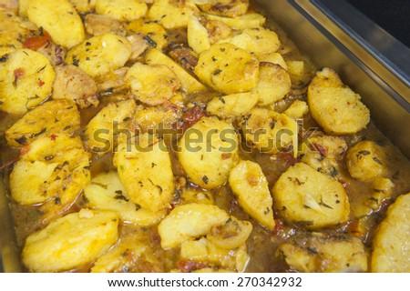 Closeup detail of moroccan potato dish on display at a hotel restaurant buffet - stock photo