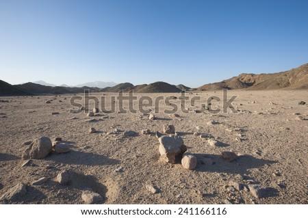 Closeup detail of stony desolate arid desert landscape with mountains - stock photo