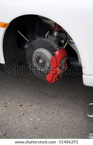 Closeup detail of the wheel assembly and six piston calipers on a modern sports car braking system. The rim is removed showing the front rotor and caliper. - stock photo
