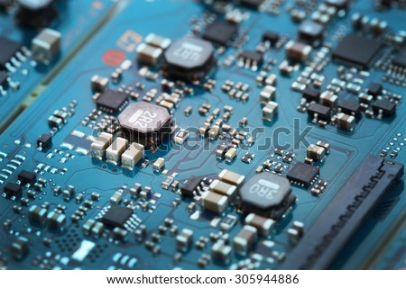 Closeup electronic circuit board, blurred and toned image. Shallow DOF, focus at three capacitor chip on the left. - stock photo