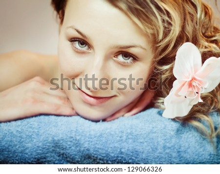 Closeup face of beautiful woman with orchid in hair