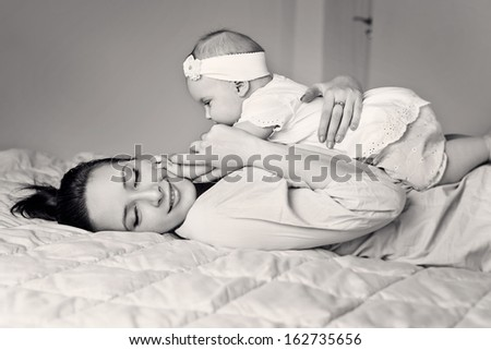 Closeup faces of young happy mother with cute newborn baby. Black and White - stock photo