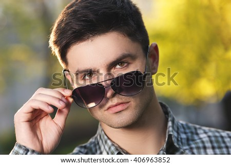 Closeup facial portrait of a guy, young man looking to camera with sunglasses - stock photo