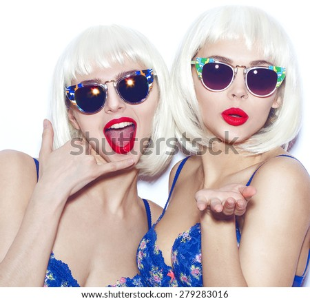 Closeup fashion lifestyle portrait of two pretty best friends girls,wearing bright swag style bra,jewelry,having fun and make crazy funny faces.Two sisters posing with red lips.Hipster.Swag style. - stock photo