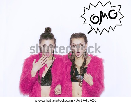 Closeup fashion lifestyle portrait of two pretty best friends girls,wearing bright swag style pink fur,having fun and make crazy funny faces.Two sisters posing on party.Hipster.Swag style.OMG sticker - stock photo