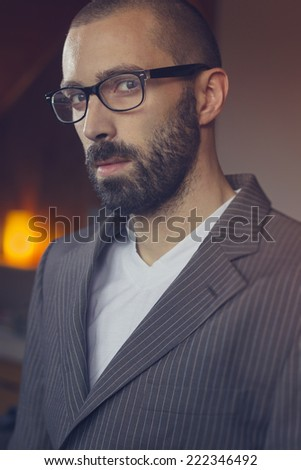 Closeup fashion portrait of a handsome man with beard, wearing suit and glasses - stock photo
