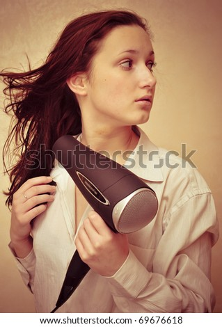 Closeup fashion portrait of young pretty woman drying her hair near a mirror - stock photo