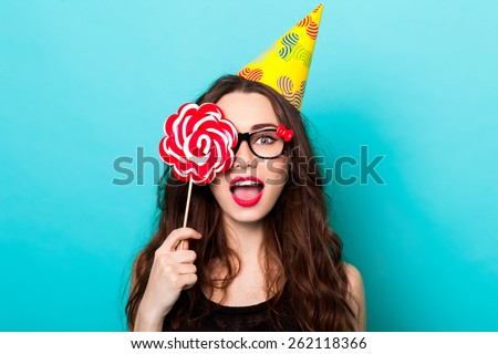 closeup fashion   portrait of young sexy funny  crazy woman posing on blue wall background in summer style outfit with pink lollipop wearing paper hat and cute glasses. - stock photo