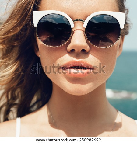 Closeup fashion summer portrait of pretty young sensual woman in sunglasses posing on the beach on vacation - stock photo