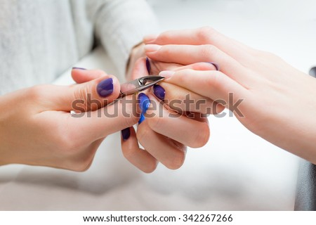 Closeup finger nail care by manicure specialist in beauty salon. Manicurist clear cuticle professional nippers for manicure and pedicure. - stock photo