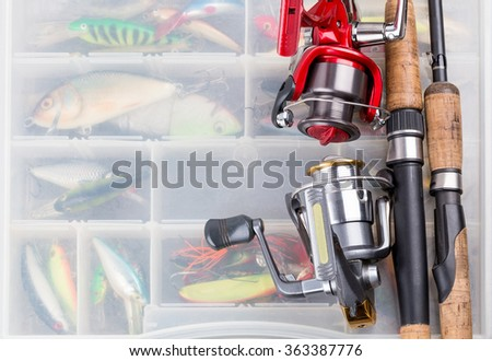 closeup fishing rod with reel on background of tackles in boxes with baits, lure, wobblers