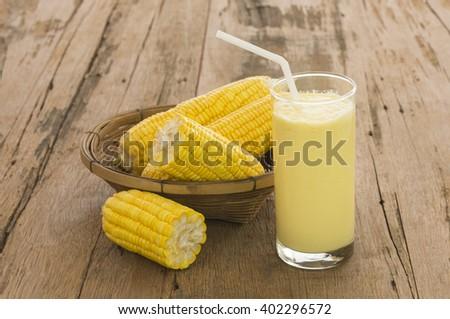 Closeup, fresh sweet corn juice (corn milk) on a wooden table. - stock photo