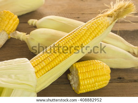 Closeup, fresh sweet corn on a wooden table. - stock photo