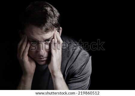 Closeup front view of mature man with head down, touching his temples, while displaying depression on black background   - stock photo