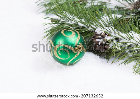 Closeup front view of single green and gold Christmas ornament with fir branch covered in snow