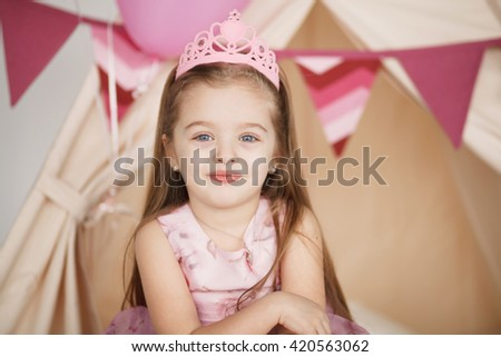 Closeup funny little princess girl in pink crown and dress posing on tent background. Preschooler close up portrait with copy space - stock photo