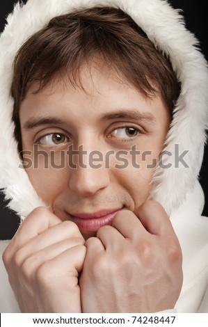 closeup funny portrait of a man in the hood on a dark background - stock photo