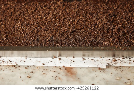 Closeup grained nuts on mold filled with melted chocolate mass. Preparation of tasty cake from organic chocolate in artisan confectionery for sale - stock photo
