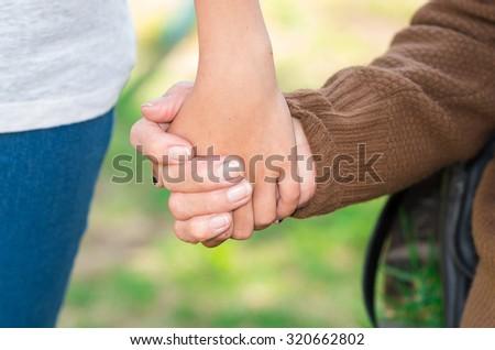 Closeup grandmother granddaughter holding hands, outdoors environment. - stock photo