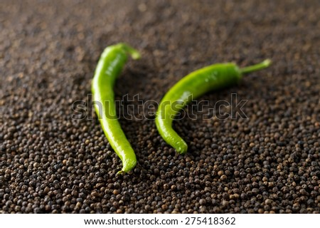 closeup green peppers on black peppercorns - stock photo