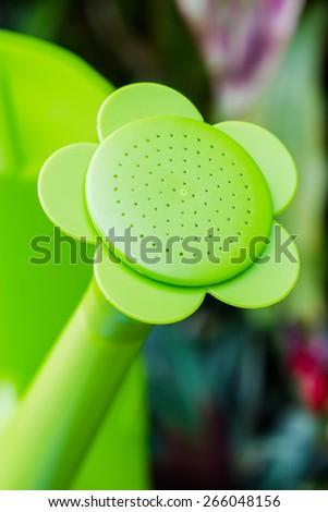 Closeup green watering can in garden - stock photo