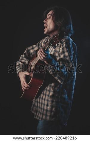 Closeup. Guitarist plays on a guitar. Selective focus - stock photo