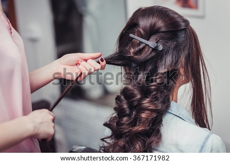 Closeup hairdresser coiffeur makes hairstyle. - stock photo