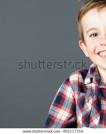 closeup half portrait of a young preschooler with freckles and blue eyes laughing for fun wellbeing and freedom, grey background studio - stock photo