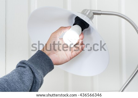 closeup hand changing an electric light bulb
