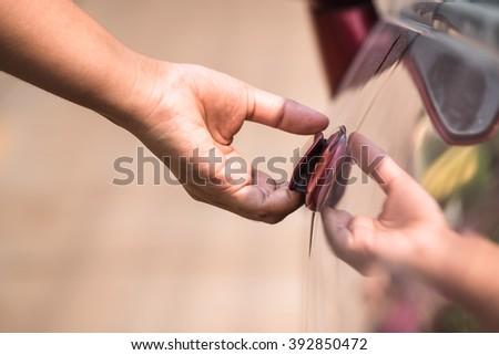 Closeup hand going to open car door - stock photo