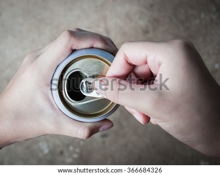 closeup hand holding and opening can