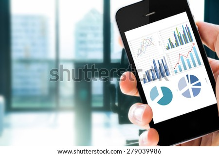 Closeup hand holding mobile phone show analyzing graph with conference room background  - stock photo