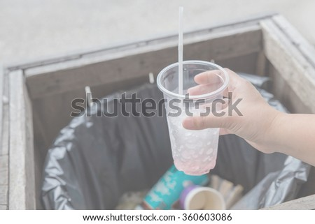 Closeup hand holding piece of garbage in trash can - stock photo