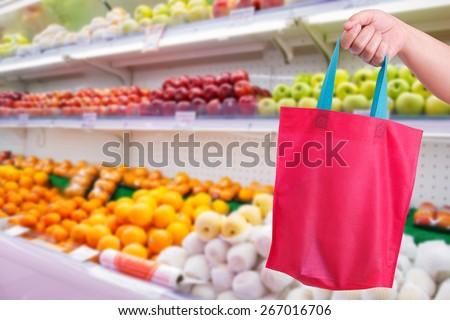 closeup hand holding reusable bag in supermarket - stock photo