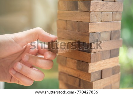 Closeup hand man take one block on The tower from wooden blocks,